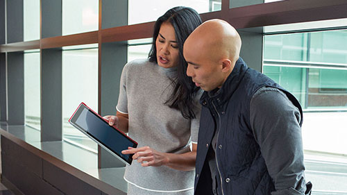 Woman showing man item on her tablet