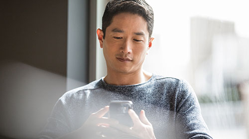 Man looking at and working on mobile device