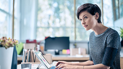 Woman looking off camera while working on Surface tablet