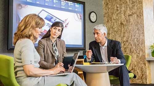 Colleagues discuss topics with laptops