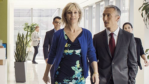 Woman leading colleagues down a hall