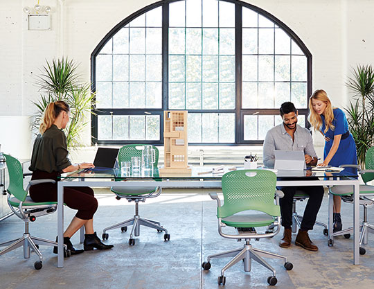 Three people working in a bright office.