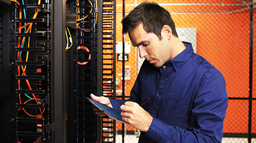 Man working on a tablet in a server room.