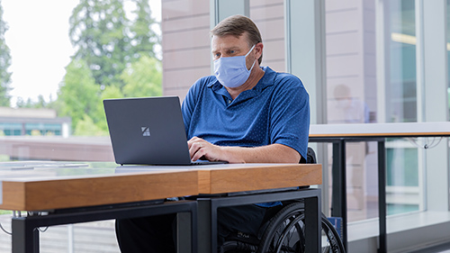 Person working with mask on Surface device