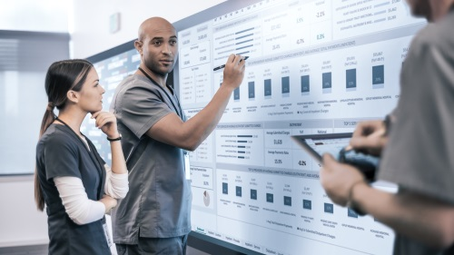 Image of a man and woman in scrubs using a Surface Hub