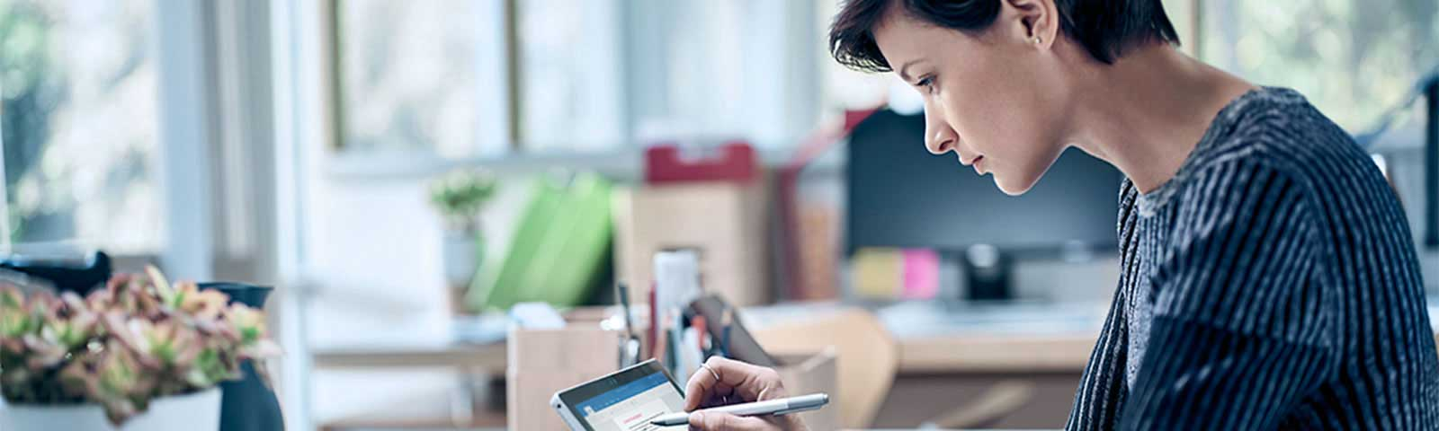 Woman using pen on surface tablet at desk