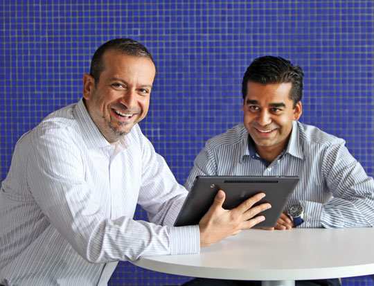 Two men sitting at computer smiling