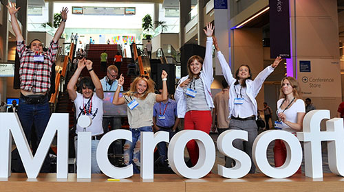 People jump behind Microsoft sign at Worldwide Partner Conference