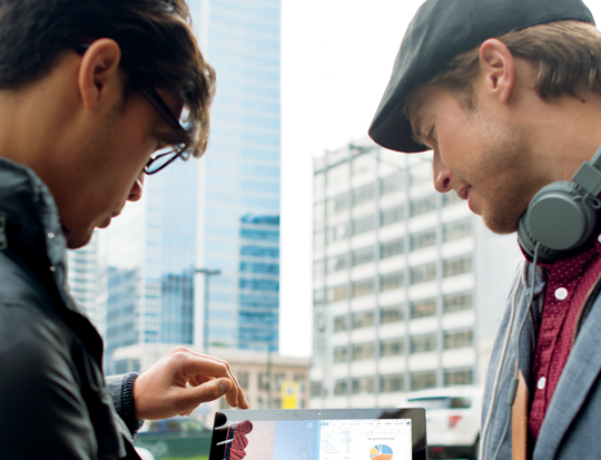 Two men look at a tablet for information about Microsoft Connect