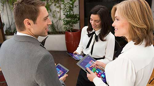 Man and two female coworkers talking and working on tablets