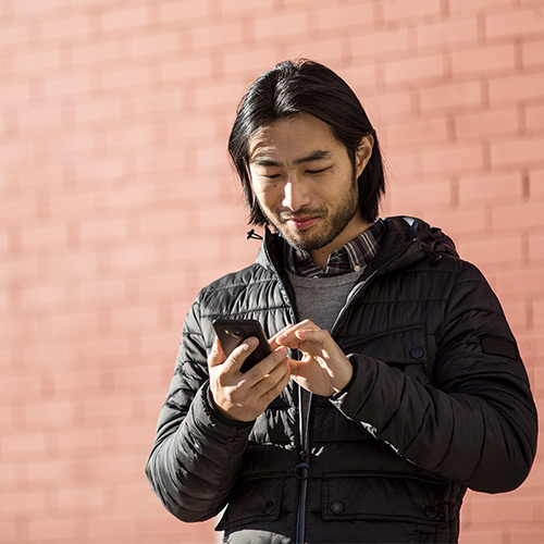 Man standing outside working on cellular device
