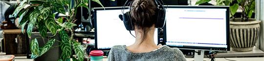 Woman at a desktop facing a monitor