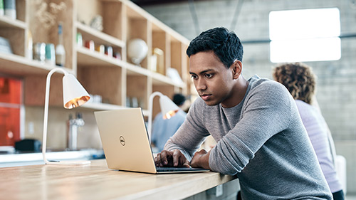 Young man sitting at desk and working on laptop