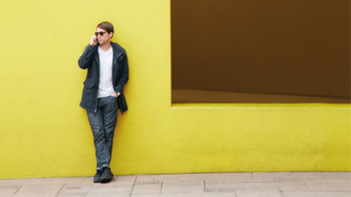 Man leaning against wall outside while talking on cell phone