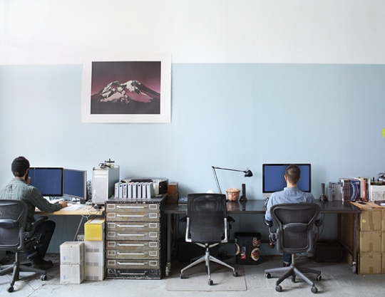 A group of people in a room working behind their desk