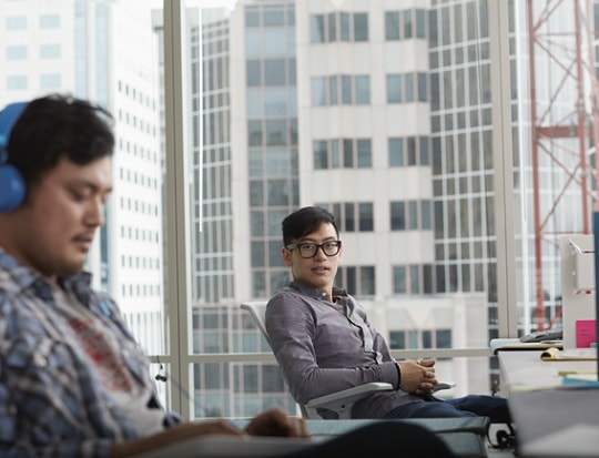 2 people collaborating behind the computer in an open office spaces