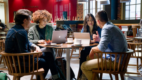 Four people having coffee and working on computers