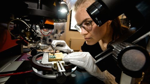 Woman working on microchips in a lab