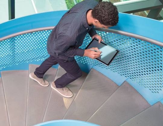 A man walking up spiral stairs using a Microsoft tablet