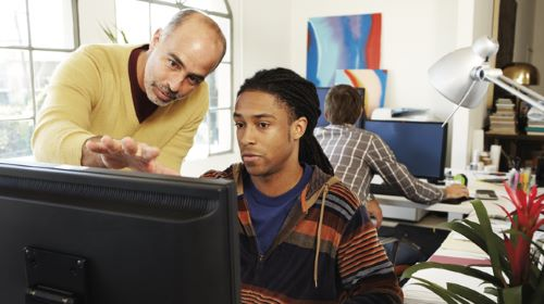 Two men looking at a computer with Microsoft Office