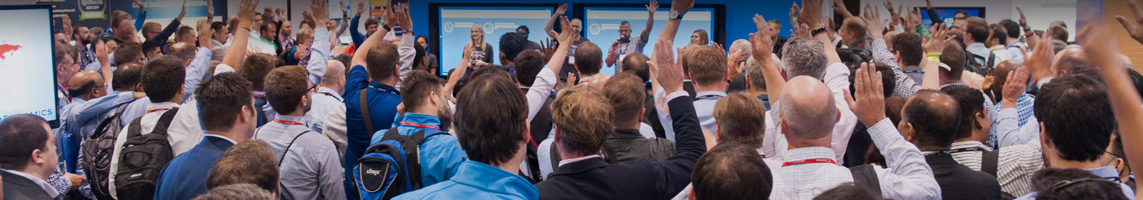 Audience members raise their hands during a session at a previous WPC event