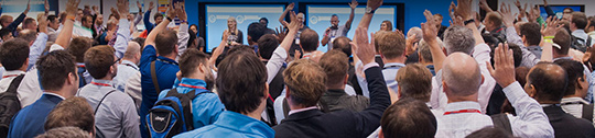 Audience members raise their hands during a session at Microsoft Inspire