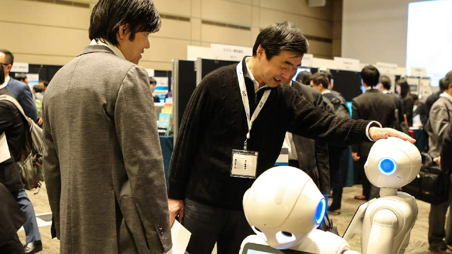 Two men looking at robots