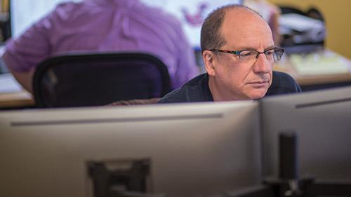 Man working at multi-monitor computer