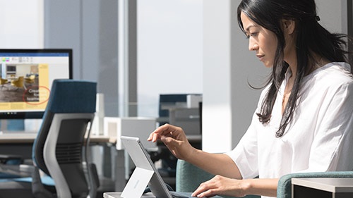 Woman at desk using Surface tablet