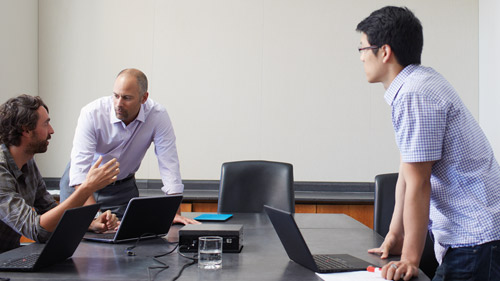 Three coworkers talking and working on laptops in conference room