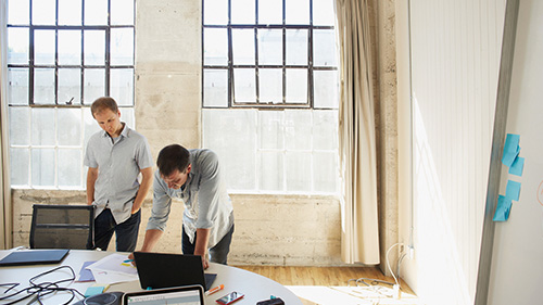 Two men working on a problem in a white office in front of windows