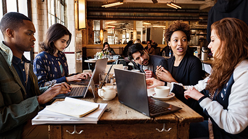 A group of young people working on Microsoft products at a café