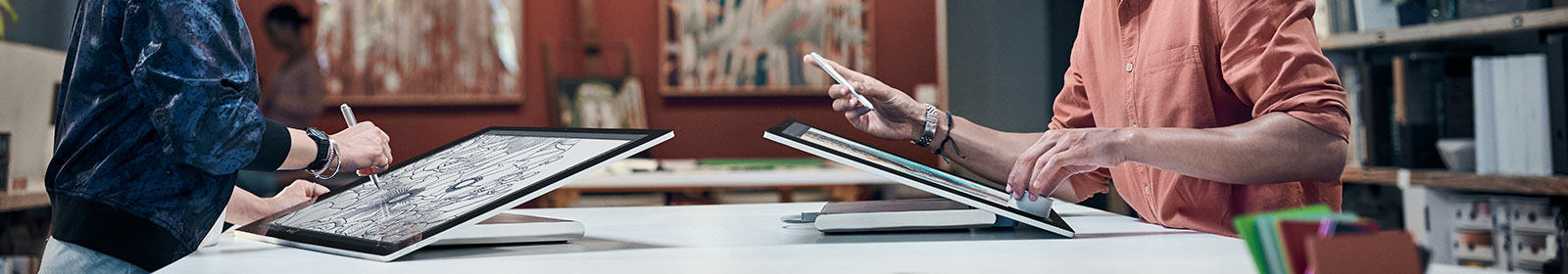 Two people drawing on tablets