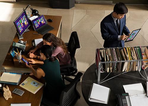 Hombres y mujeres de negocio que usan los productos y soluciones de Microsoft