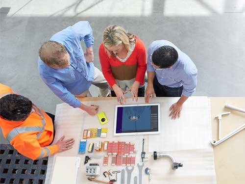 Construction and architects gathered around table working on tablet