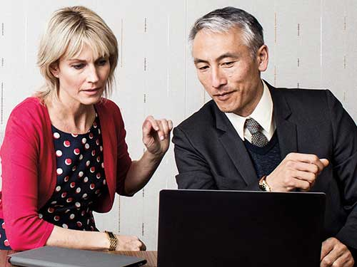 Man and woman coworkers working on surface tablet in meeting room