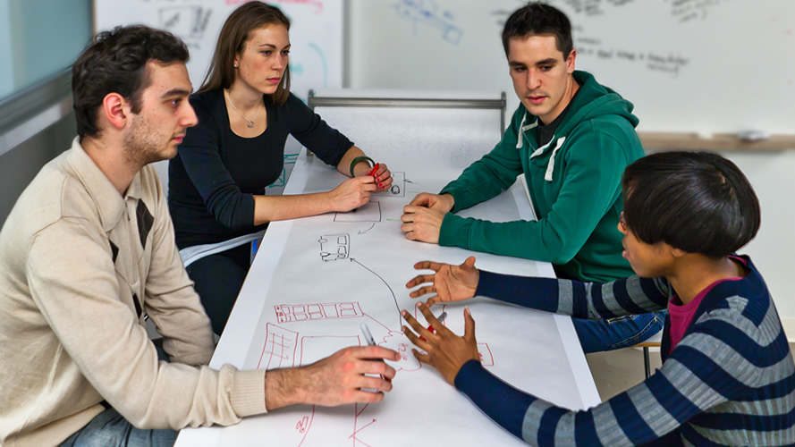 A team sits around a table and plans their project