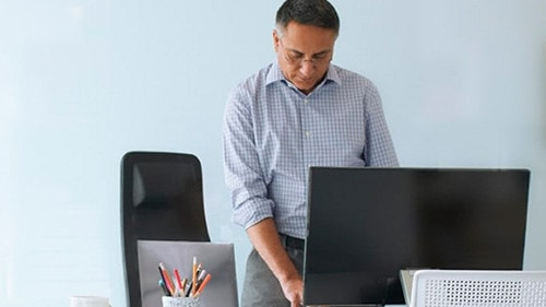 Man standing working at a computer.