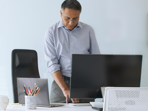 Man standing at desk with desktop and Surface laptop