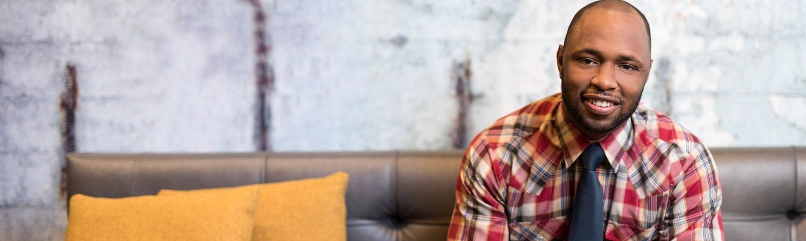Smiling man in plaid shirt