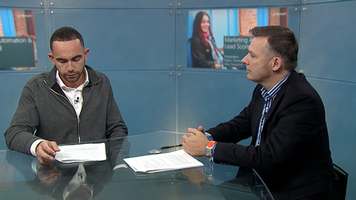 Two men at a desk talking in front of camera