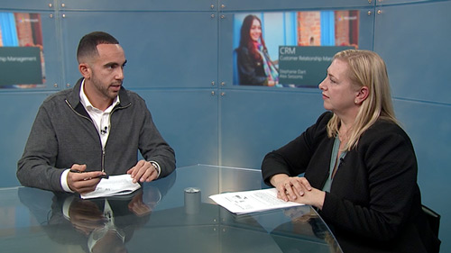 Man and woman sitting at a desk having discussion in front of camera