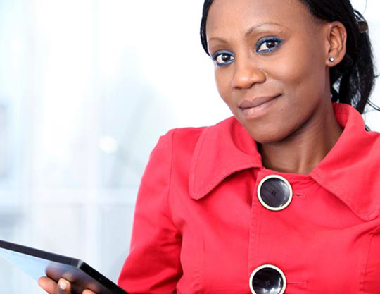 Woman posing for photo while working on Surface tablet