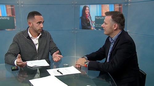 Two men sitting at a desk talking in front of camera