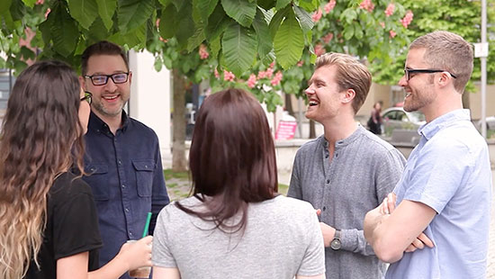 A group of coworkers standing outside under a tree, smiling and laughing