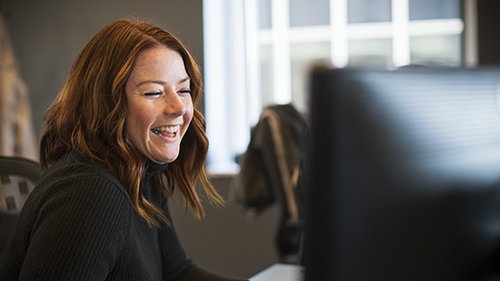 Young woman smiling while working at desktop screen