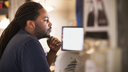 Man sitting and thinking while working on laptop