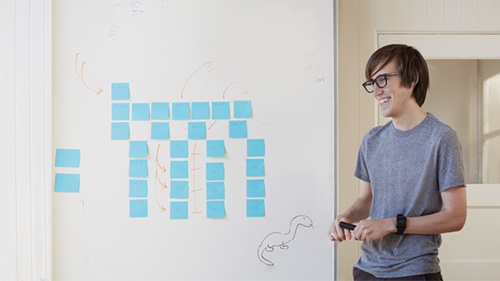 Young man standing in front of whiteboard smiling