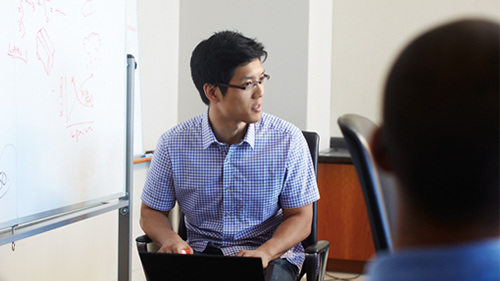 Young man sitting in front of whiteboard working on laptop