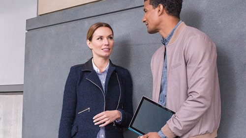 Two coworkers standing outside talking and holding Surface tablets